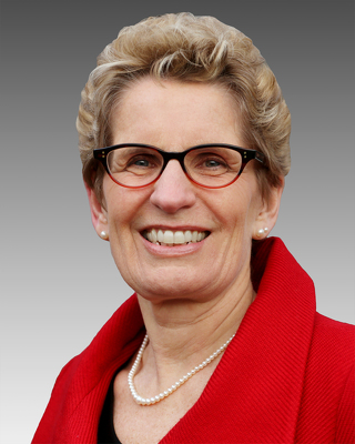 image Kathleen Wynne Premier of Ontario wearing pearls, glasses,red shirt
